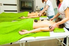 Massage met hete rotsenstenen in schoonheidsspecialist Stock Afbeeldingen