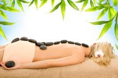 Massage mit heißen vulkanischen Steinen Stockfotografie