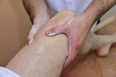 Massage mit vulkanischen Steinen und den Händen Lizenzfreies Stockfoto