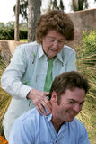 Massage From Mom. A loving mother massaging her adult son's shoulders. (focus is on mother Royalty Free Stock Image