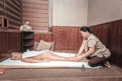 Nice Asian woman warming up legs muscles. During the massage. Nice Asian women warming up legs muscles while doing the body massage royalty free stock images