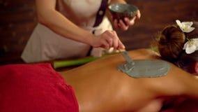 Massage- och lerakroppmaskering i brunnsortsalong stock video