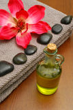 Massage oil. In bottle with massage stones a towel and a flower on wooden background stock photos