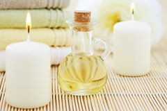 Massage oil. Bottle of massage oil with towels and flower - beauty treatment royalty free stock image