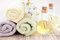 Massage oil. Bottles of massage oil with towels - beauty treatment royalty free stock photo