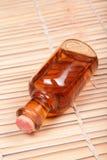 Massage oil. Bottle of massage oil on wooden background stock image