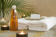 Massage oil with candles and palm branch Royalty Free Stock Photos