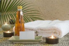 Massage oil with card holder. Massage oil and towels with candles at spa stock photos