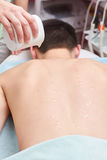 Massage oil drops on skin. Back of healthy man stock image