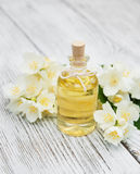 Massage oil with jasmine flowers. On a wooden background royalty free stock image