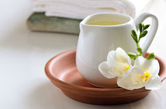 Massage oil in a jug. Massage oil in a white jug decorated with fresh flower royalty free stock images