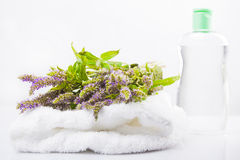 Massage oil and melissa flowers on a towel.  Royalty Free Stock Photo