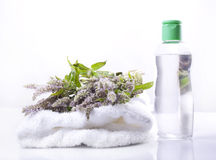 Massage oil and melissa flowers on a towel.  Royalty Free Stock Images