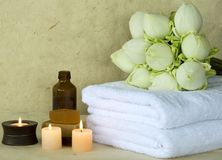 Massage oil products. Lotus flower massage oil and spa towels Royalty Free Stock Images