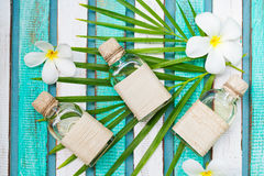 Massage oil set with palm leaf, flowers. Top view royalty free stock photo