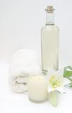 Massage Oil Spa. Massage oil, towel and relaxing spa candle to show benefits of spa cleansing for health Stock Photos