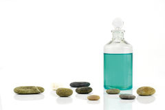 Massage oil and stones. Green massage oil and stones on white background stock photo
