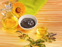 Massage oil and therapeutic clay mud black flowers. Green towel on wooden table stock photos