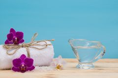 Massage oil and towel for spa treatments, on a blue background stock image