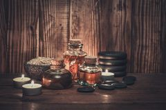 Massage oil in vintage bottle. Candles and stones for stone massage on wooden background Royalty Free Stock Photography