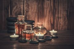 Spa concept. Massage oil in vintage bottle, candles and stones for stone massage on wooden background Stock Photos