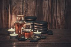 Spa concept. Massage oil in vintage bottle, candles and stones for stone massage on wooden background Royalty Free Stock Image
