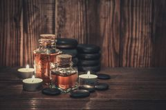Massage oil in vintage bottle. Candles and stones for stone massage on wooden background Royalty Free Stock Photo