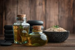 Massage oil in vintage bottle. Sea salt and stones for stone massage on wooden background Stock Photos
