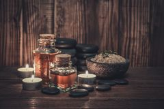 Massage oil in vintage bottle. Sea salt and stones for stone massage on wooden background Stock Photography