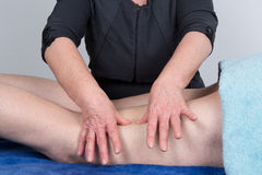 Massage patient's leg at spa center Royalty Free Stock Image