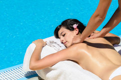 Massage relax at poolside. Woman receives massage in spa club near pool in summer Stock Image