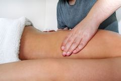 Masseuse hands massaging female back. Massage relax studio. Massage back. Young women receiving back massage at spa. Masseuse hands massaging female back Royalty Free Stock Photos