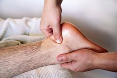 Male foot massage in spa salon. Massage relax studio. Foot massage. Close up of foot receiving massage in spa salon. Man receives leg massage. Therapists hands Royalty Free Stock Photo