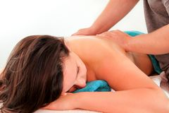Woman laying on massage table and having a massage back. Massage relax studio. Woman laying on massage table and having a massage back. Beautiful girl is enjoys Royalty Free Stock Images