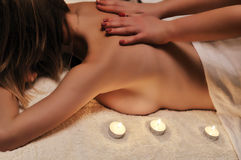 Massage in semi-darkness with candles Stock Images