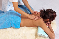Massage of shuolder. Masseur doing massage on female shoulder in the beauty salon Royalty Free Stock Photo