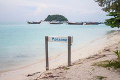 Massage sign on the sunrise beach with longtail boat in the background at Lipe island, Satun Province, Thailand royalty free stock photography