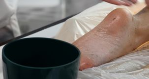 Massage specialist doing massage of womans feet with scrub at beauty spa.  stock video