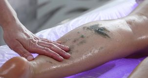 Massage specialist doing massage of womans feet with scrub at beauty spa.  stock footage