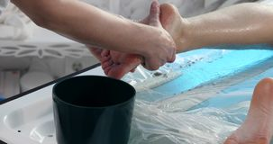 Massage specialist doing massage of womans feet with scrub at beauty spa.  stock video footage