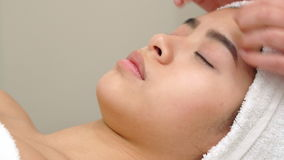 Massage specialist stokes girl`s forehead. Massage specialist stroking girl`s forehead at the beauty salon. Close up of female hands massaging woman`s skin over stock footage