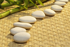 Massage stones. A line of massage stones on woven mat with bamboo in the background Royalty Free Stock Image