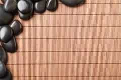 Massage stones on bamboo mat Stock Image