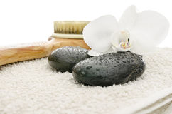 Massage stones, brush and orchid on a towel Stock Photography