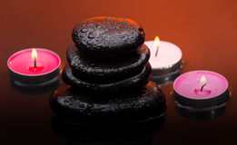Massage stones with burning candles and water drops Stock Photography