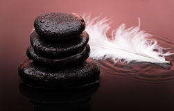 Massage stones with feather and water drops.  royalty free stock image