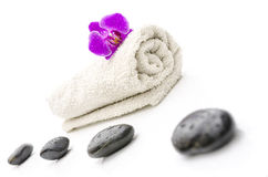 Massage stones and violet orchid flower on a towel Stock Images