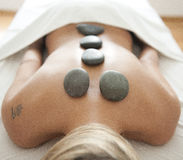 Massage with stones. Woman`s back with massage stones Stock Photos
