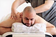 Massage therapist massaging shoulders of a male athlete. Massage studio. Sports massage. Massage therapist massaging shoulders of a male athlete, working with Stock Photography