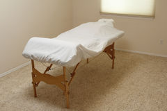 Massage Table in a Treatment Room. Professional wood legged massage table set up in a massage office and covered in white sheets over a bolster and body cushion Stock Photos